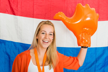 Sports fan Wearing an Inflatable orange Hand Cheering in front o