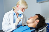Dentist examining patient with toothache