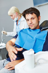 Man at dentist reaching for cup of water