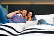 Young couple in Hotel in bed with phone and computer