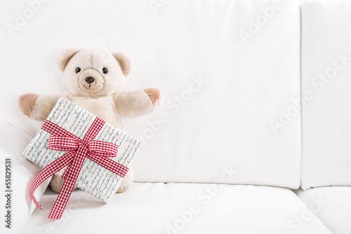Teddybär als Geburtstagskarte mit Geschenk als Hintergrund