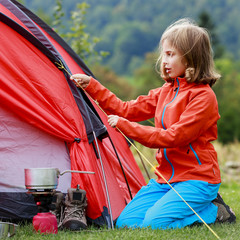 Camp in the tent - young girl setting a tent
