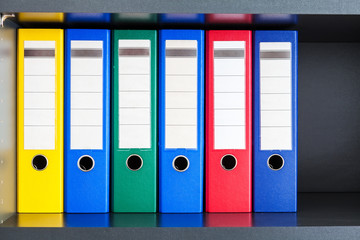 Red, green, blue and yellow office folders with boxes