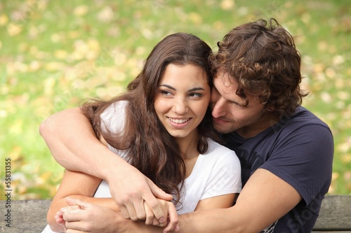 Couple cuddling in love in a park