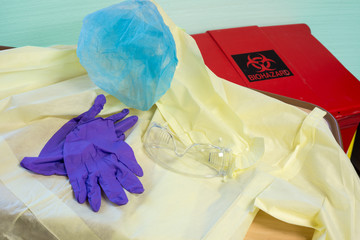 Disposable hospital gown, gloves, hair cover and goggles next to