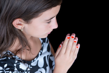 Hispanic girl praying with her eyes closed isolated on black