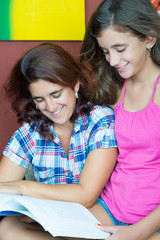 Latin mother and her daughter reading a book