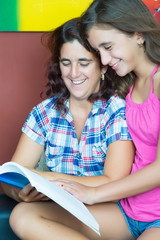 Hispanic mother and her  daughter reading a book