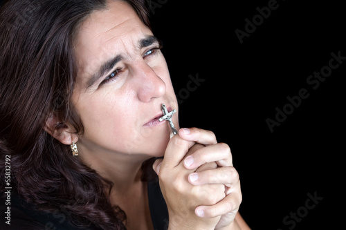 Hispanic woman praying and kissing a crucifix