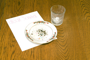 Christmas Cookie Crumbs and Empty Milk Glass on Table