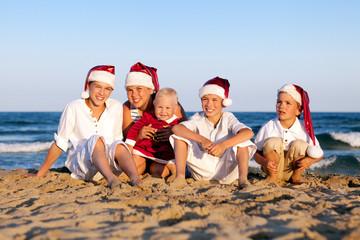 Children in santa claus hat are sitting on beach
