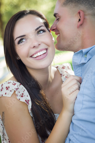 Mixed Race Romantic Couple Whispering in the Park