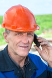 View of mature manual worker in orange hardhat calling on phone