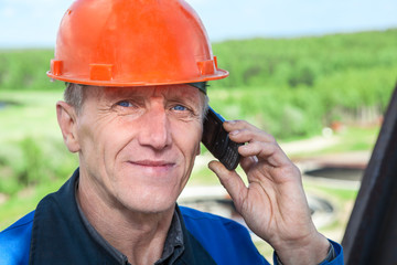 View of senior manual worker in hardhat calling on phone