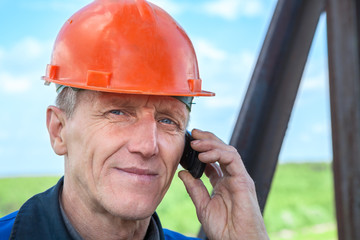 Senior manual worker in orange hardhat calling on the phone
