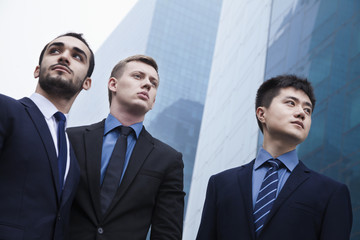 Portrait of three serious businessmen, outdoors, business district