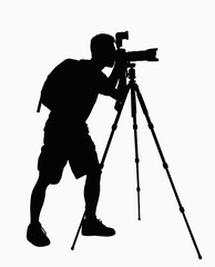 Silhouette of man taking pictures with camera on tripod.