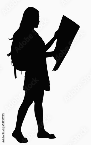 Silhouette of woman looking at map.