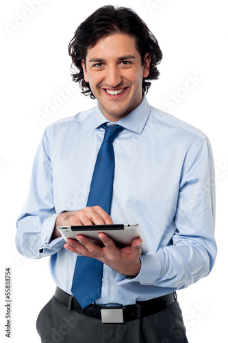 Young businessman operating tablet device