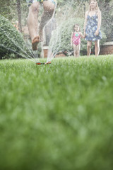 Surface level shot of father jumping through a sprinkler in the grass, mother and daughter watch in the background