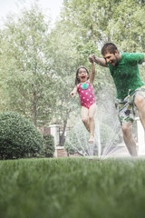 Father holding daughters hand while she jumps through the sprinkler in the garden