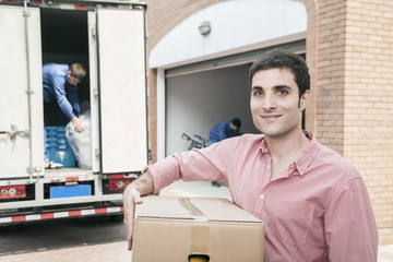 Smiling man holding a cardboard box and moving into his new home