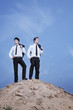 Two young businessmen standing on the top of the hill in the desert