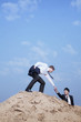 Young businessman helping another businessman get to the top of the hill in the desert