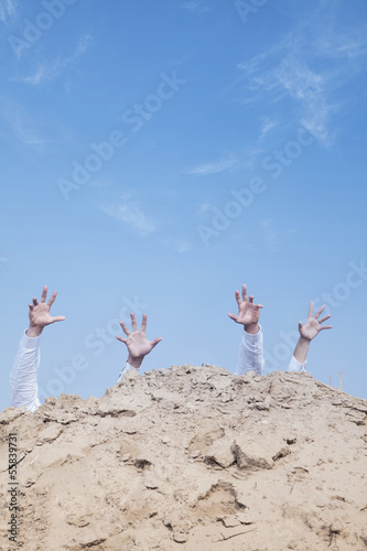 Close-up of hands of businessmen behind a hill in the desert, reaching upwards