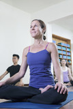 Woman sitting cross-legged in a yoga class