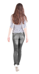 back view of walking  woman in jeans .
