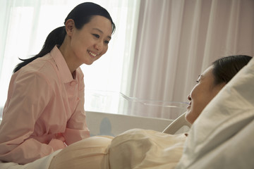 Smiling nurse talking to pregnant woman lying on bed in the hospital