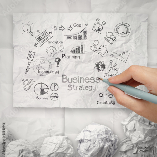 hand drawing creative business strategy on crumpled paper backgr