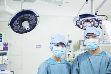 Portrait of two surgeons wearing surgical masks in the operating room, looking at camera