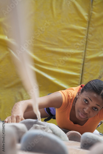 Determined young woman climbing up a climbing wall in an indoor climbing gym, directly above