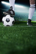 Close up of feet on top of soccer ball, night time in the stadium