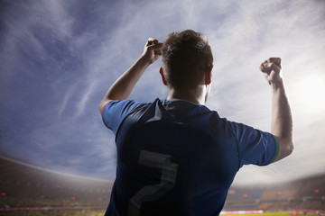 Soccer player with arms raised cheering, stadium with sky and clouds