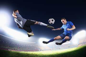 Two soccer players in mid air kicking the soccer ball, stadium lights at night in background