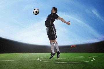 Soccer player hitting the ball with his chest in the stadium, day time