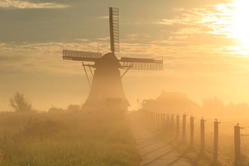 Windmill at foggy sunrise
