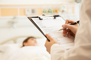 Close up of doctor writing on a medical chart with patient lying in a hospital bed in the background