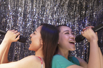 Two friends back to back holding microphones and singing together at karaoke