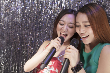 Two friends holding microphones and singing together at karaoke