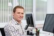 Leinwandbild Motiv lächelnder mann am arbeitsplatz