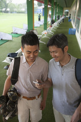 Two male friends smiling and getting ready to leave the golf course, looking down at phone
