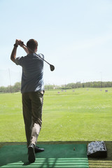 Rear view of young man hitting golf balls on the golf course, arms raised