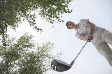 Low angle view of man getting ready to hit the golf ball on the golf course