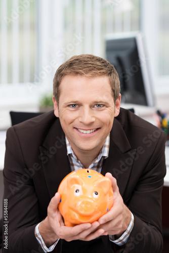 lächelnder mann im büro mit sparschwein