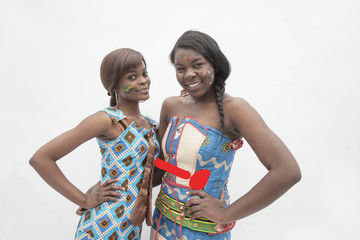 Portrait of  two young smiling women with hands on their hips in traditional dresses from Africa, studio shot