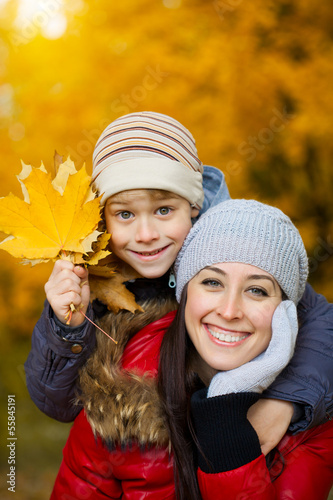 happy Mom and son are playing in a yellow autumn